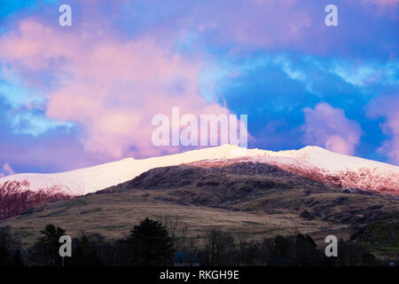 Pink clouds at sunset above snow capped Mount Snowdon in winter in mountains of Snowdonia National Park. Rhyd Ddu, Gwynedd, North Wales, UK, Britain - Stock Image