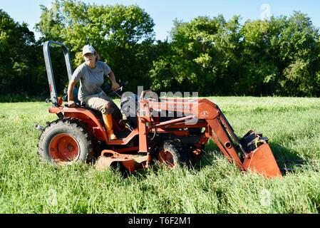 Hard working woman farmer standing up and hopping off after driving a Kubota orange tractor on small farm outside Decorah, Iowa, USA - Stock Image