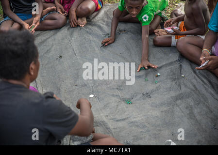 Women and boys playing with marbles,  Korogo Village, Middle Speik, Papua New Guinea - Stock Image