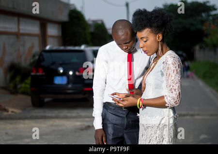 Two business colleagues using a mobile phone outside on the street. - Stock Image