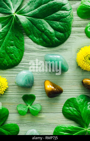Green Aventurine and Tiger's Eye with Shamrocks and Yellow Chrysanthemums - Stock Image