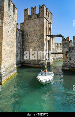 SIRMIONE, LAKE GARDA, ITALY - SEPTEMBER 2018: People in a motor boat cruising past the Scaliger Castle in the centre of Sirmione on Lake Garda. - Stock Image