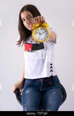 Young girl with retro clock in hand showing time on yellow clock isolated on white background. Woman is blurred motion. Close up, selective focus - Stock Image