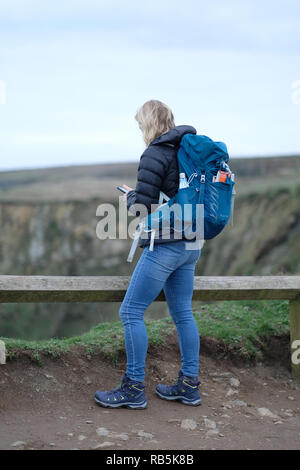 A young woman wearing a rucksack on National Trust Property. - Stock Image
