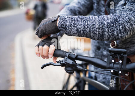 A close-up of a cyclist with electrobike putting on black gloves outdoors in town. - Stock Image