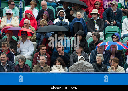 A crowd of spectators at a tennis match shelter in rain jackets and under umbrellas during a break in play - Stock Image