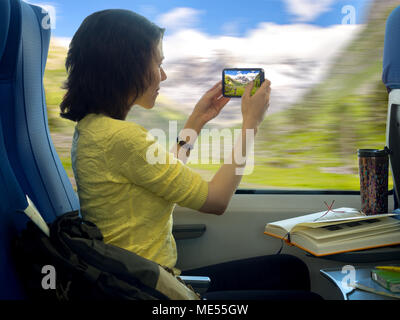 Young woman with smartphone making photos of beautiful scenery during traveling in train near window - Stock Image