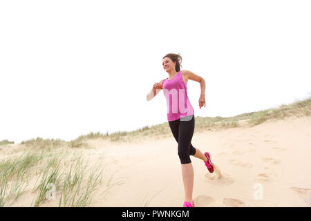 Young woman running on the beach - Stock Image