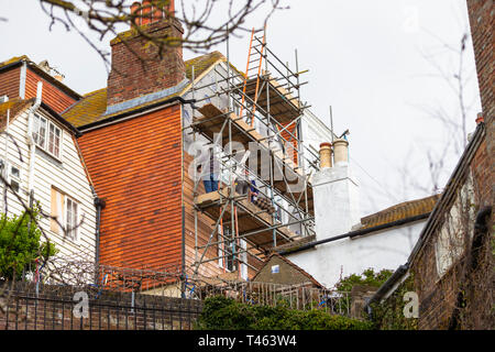 Workmen working at height on scaffolding fixing new weatherboards to a building, hastings, east sussex, uk - Stock Image