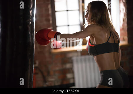 A woman boxer hitting the punching bag in the gym on the training - Stock Image