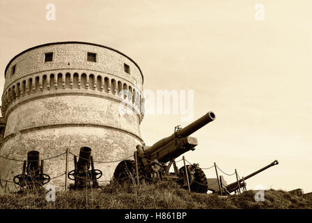 old guns under the old tower with cloudy sky - Stock Image