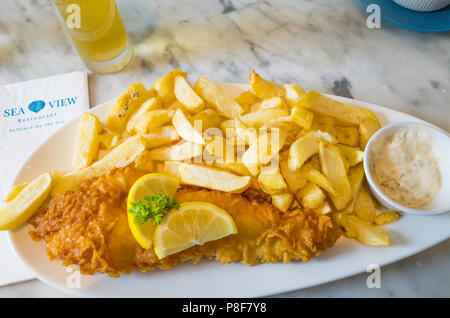 Fried Haddock and Chips and half a pint of lager traditional seaside meal at the Seaview Café Saltburn North Yorkshire UK - Stock Image