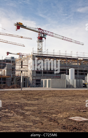 Large construction site with scaffolding building, yellow tower crane and clear blue sky. - Stock Image