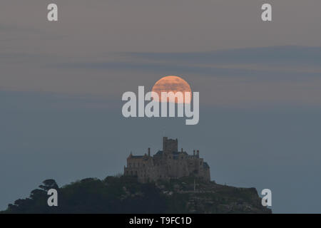 Long Rock, Cornwall, UK. 18th May 2019. UK Weather. The full flower moon, also a blue moon, seen rising above St Michaels mount this evening. Credit Simon Maycock / Alamy Live News. - Stock Image