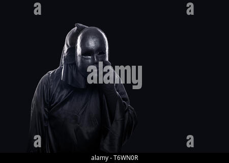 Scary figure in hooded cloak with mask in hand isolated on black background - Stock Image