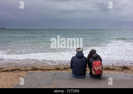 A young couple sitting and looking at sea, Saint Malo, Brittany, France - Stock Image