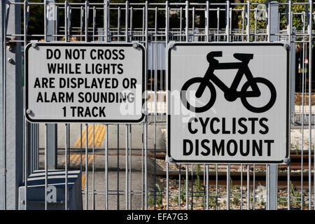 Warning signs for cyclists at a railway crossing. - Stock Image