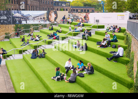 London, UK - October 2017: Young People students sitting outdoor on Granary Square steps. Granary Square is a public square on the banks of Regent's C - Stock Image