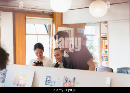 Creative designers reviewing photograph proofs in office - Stock Image