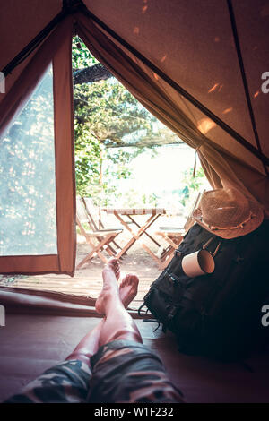 vertical view of crossed feet of a hiker man resting barefoot in a camping tent, travel discovery concept, point of view shot - Stock Image