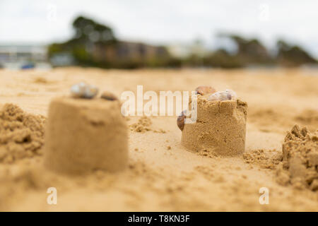 Selective focus colour photograph of two sand castle turrets on beach with only one in focus on cloudy day. - Stock Image