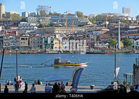 A view of a boat on the River Douro, Vila Nova de Gaia houses on riverside, people sitting on Ribeira waterfront quay Porto Portugal EU   KATHY DEWITT - Stock Image