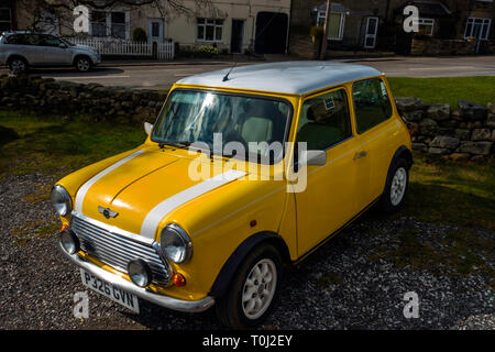 A 1996 registered bright yellow and white BMC Mini Cooper saloon car - Stock Image