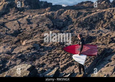 A surfer standing on rocks carrying his snapped surfboard at North Fistral in Newquay Cornwall. - Stock Image