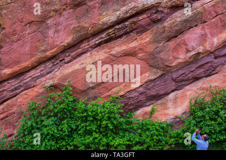 A tourist at Red Rocks Amphitheater in Morrison Colorado stops to take a picture of the colorful rock formations. Photo was taken in May. - Stock Image