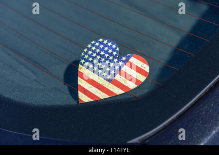 Heart-shaped stars and stripes sticker, dirty, on car window - Stock Image