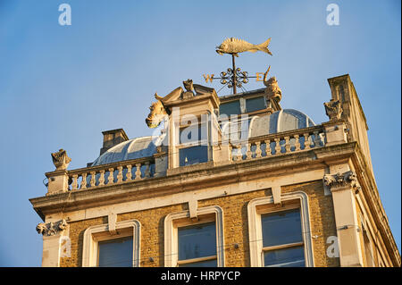 Old building with fish as a weather vane - Stock Image
