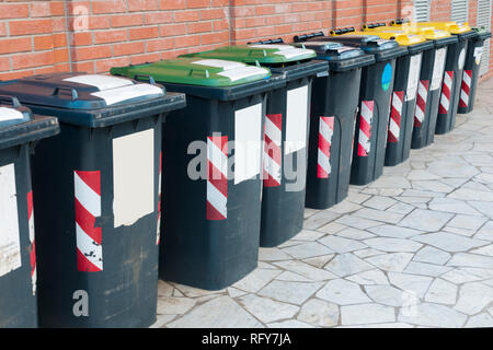Row of bins for the separate collection of glass, paper and aluminum outside a building - Stock Image