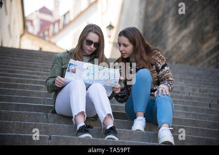Two young traveling women sitting on stairs and looking at the map. Mid shot - Stock Image