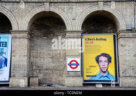 An advertising board under an archway on a platform which is no longer used at South Kensington London Underground Station - Stock Image
