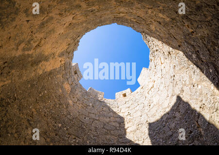 battlements of castle tower seen from below, as a circle with blue sky, in Penaranda de Duero village, landmark and public monument from eleventh cent - Stock Image