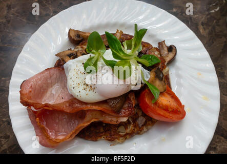 Morning snack in a café Breakfast Rosti with bacon tomato chestnut mushrooms and a poached egg - Stock Image
