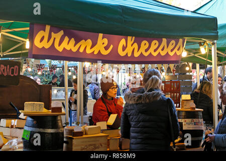 Young women serving a customer at the DRUNK CHEESES  Italian cheese stall at Borough Market Christmas food markets  in South London England UK - Stock Image