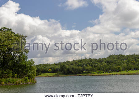 View across lake showing trees, sky and clouds - Stock Image