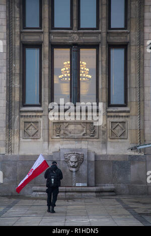 Warsaw, Poland, 11 November 2018: celebrations of Polish Independence Day. Man holding Polish flag in front of Palace of Culture and Science in Warsaw - Stock Image