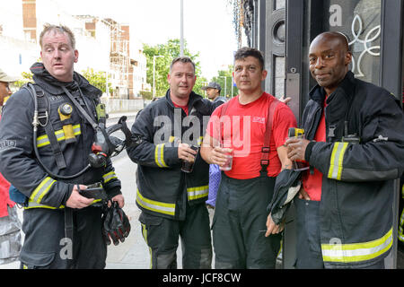 London, UK. 15th June, 2017. Firefighters resting and having a drink after working at Grenfell Tower. Credit: Hoyer - Stock Image