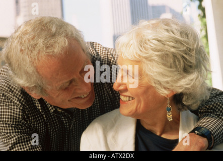 Senior couple smiling at each other - Stock Image