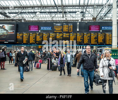 Passengers in the concourse in front of a departures board in Edinburgh Waverley Railway Station, Scotland, UK - Stock Image