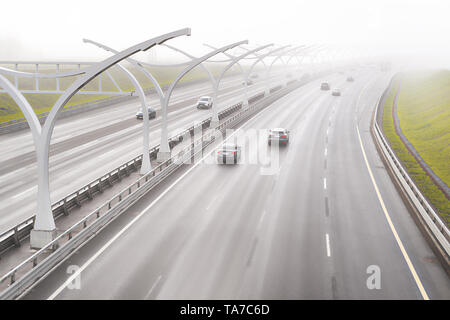Fog on highway road. Bad weather and dangerous traffic situation theme - Stock Image