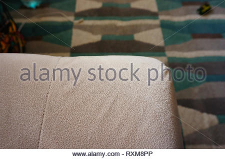 Edge of a soft couch in a room with carpet floor in soft focus background. - Stock Image