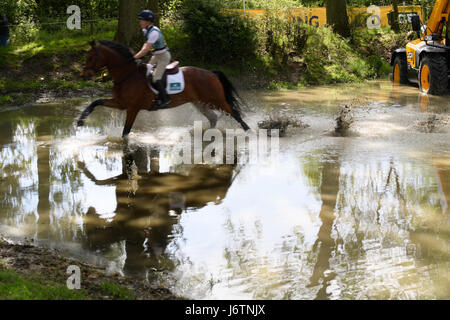 Rockingham Castle, Corby, UK. 21st May, 2017. Rider Alex Dance and his horse Count Danilo trot through the water - Stock Image
