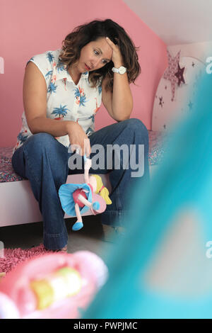 Sad woman sitting on bed in a child's room - Stock Image
