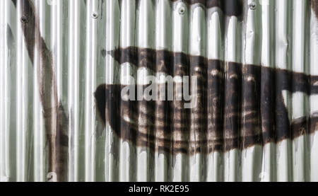 Corrugated iron wall with graffiti detail as a background. Silvery fence. Wavy metal sheet sprayed by brown color. Close-up of pop art in city street. - Stock Image