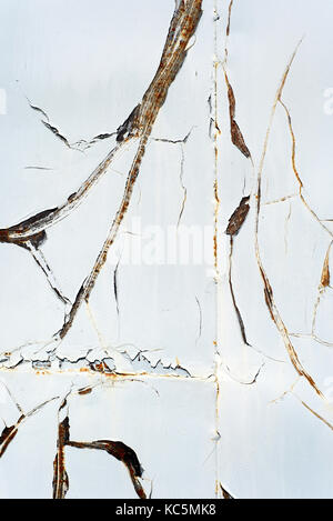 Cracked paintwork with streaks of orange rust appearing from the crevices - Stock Image