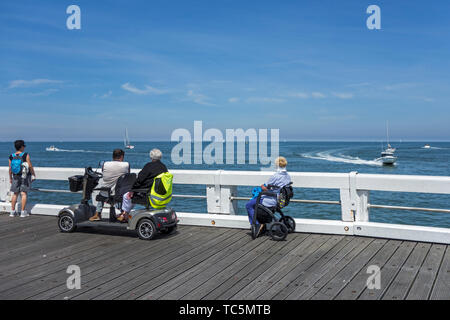 Disabled woman in wheelchair and handicapped persons in duo two person mobility scooter watching boats at sea from jetty - Stock Image