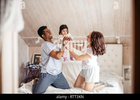 peasant gorgeous family having fun with a little kid, positive mood in the bedroom - Stock Image